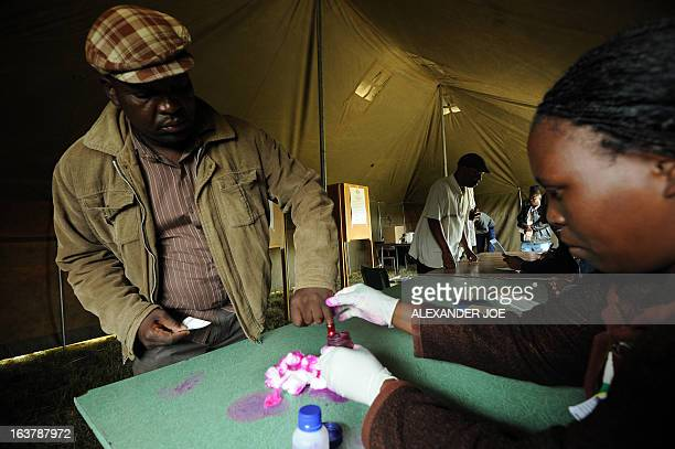 A man has his finger marked with a ink before voting in Chitungwiza on March 16 as voting kicked off for Zimbabweans referendum for a new...