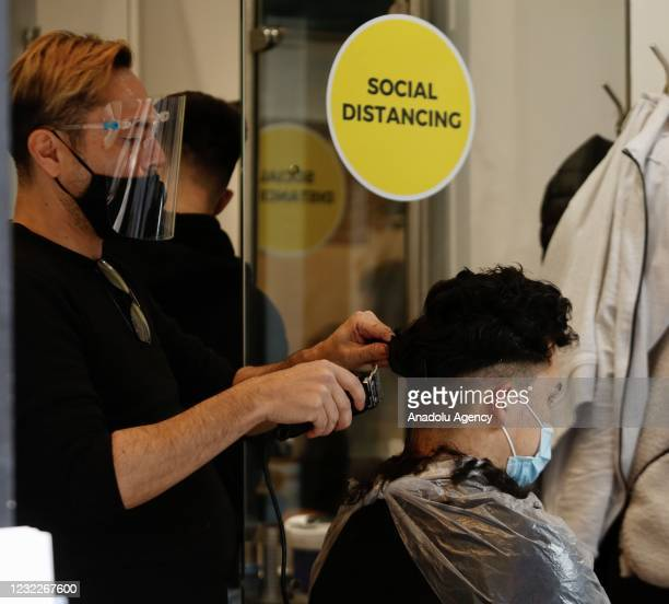 Man has his hair cut at the barbershop after the country enters the second stage of the government's roadmap out of the countryâs third nationwide...