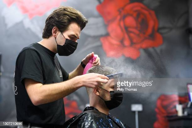 Man has his hair cut in a salon on March 15, 2021 in Cardiff, Wales. Hairdressers in Wales can resume work today after having to put down their...