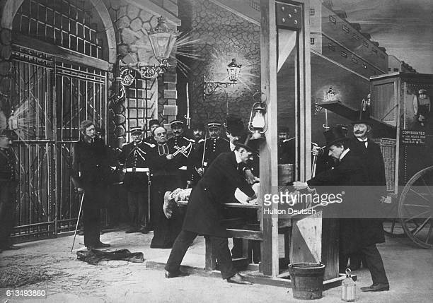 A man has his head placed under a guillotine in a scene from a film by the early French cinematographer Georges Melies