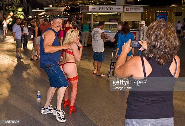 A man has his photo taken with a woman dressed in a provacative devil outfit at the Fremont Street Experience on June 22 2012 in Las Vegas Nevada...