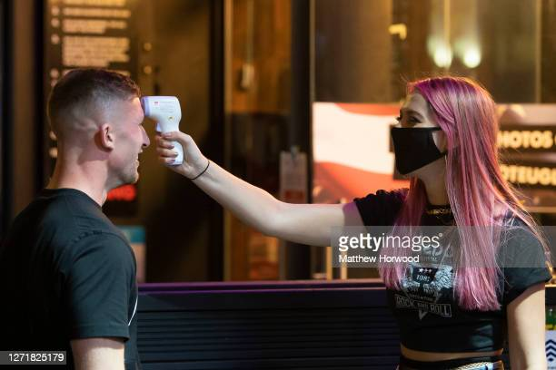Man has his temperature checked before entering the Coyote Ugly bar on St. Mary's Street on September 10, 2020 in Cardiff, Wales. In a tightening of...