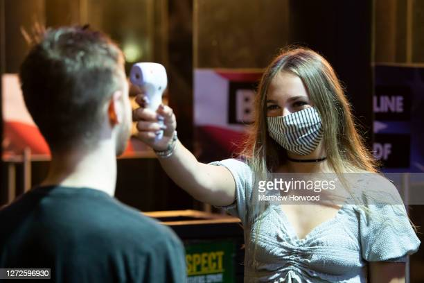 Man has his temperature checked by a woman wearing a face covering before entering Coyote Ugly bar on September 11, 2020 in Cardiff, Wales. In a...