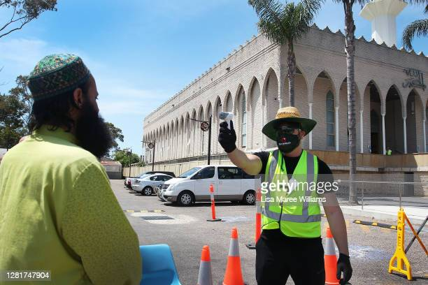 A man has his temperature checked on arrival to a midday sermon at Lakemba Mosque on October 23 2020 in Sydney Australia Religious communities across...