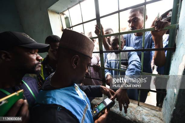 A man has his thumb print verified through the window to vote at a polling station in Kano commercial capital of northern Nigeria on February 23 2019...