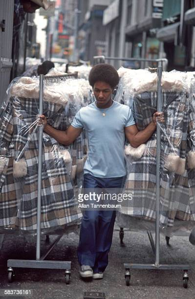 A man hauls clothing racks along the sidewalk in the Garment District New York New York August 30 1979