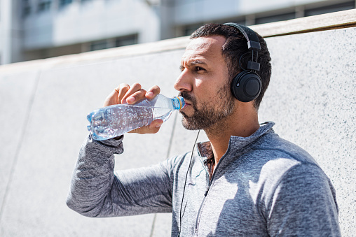Man having a break from exercising wearing headphones and drinking from bottle - gettyimageskorea