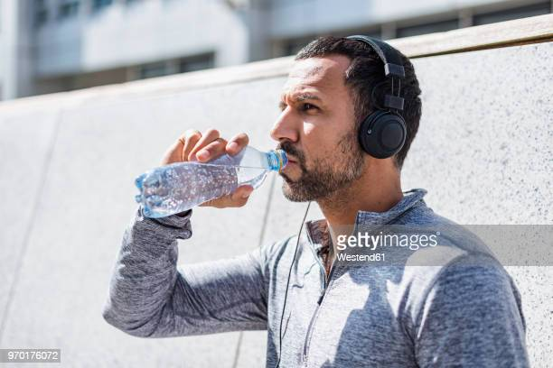 man having a break from exercising wearing headphones and drinking from bottle - einzelner mann über 30 stock-fotos und bilder