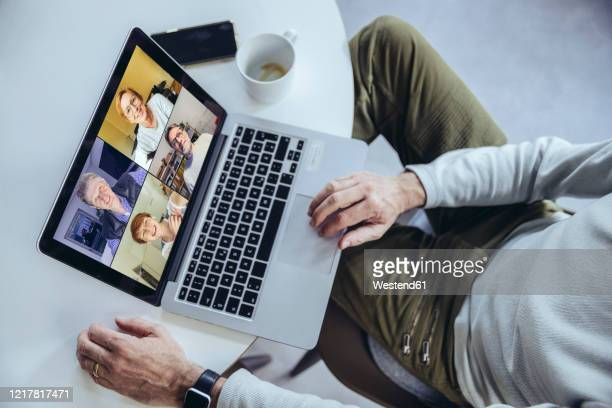 man having a conference call at home, using laptop - テレビ会議 ストックフォトと画像