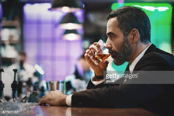 Man having a drink in a bar.