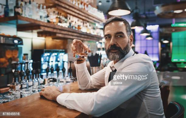 man having a drink in a bar. - whisky stock photos and pictures
