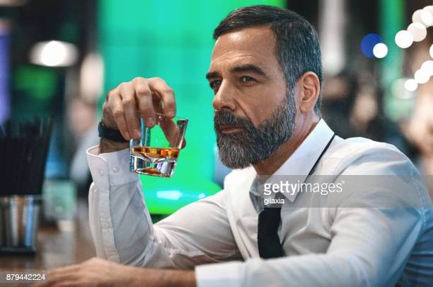 man having a drink in a bar. - masculinity stock pictures, royalty-free photos & images