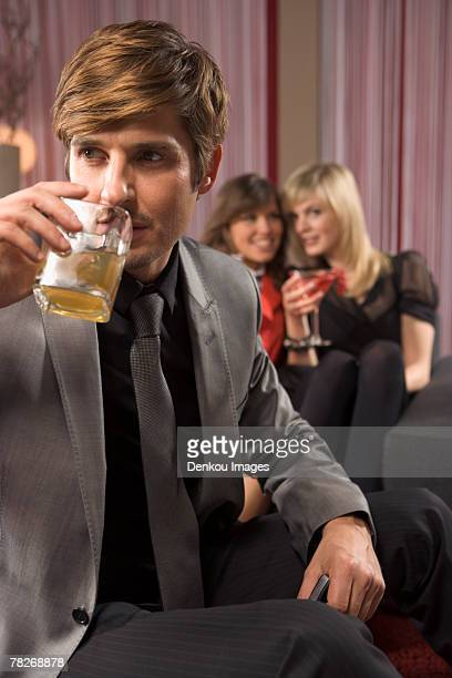 Man having a drink, women in the background