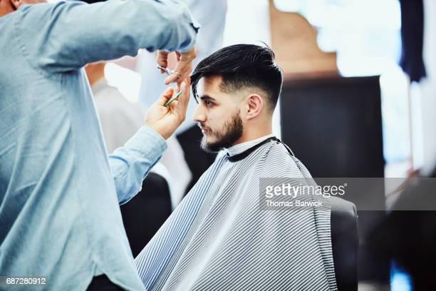 Man having a hair cut in barber shop