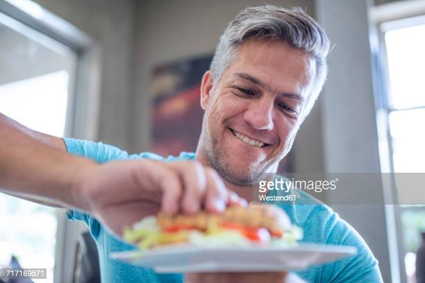 Man having a sandwich from plate