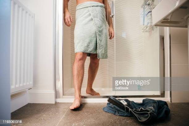 man having a shower - wrapped in a towel stock pictures, royalty-free photos & images