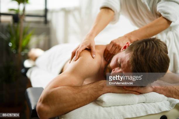 man having back massage at the health spa. - massaggi foto e immagini stock