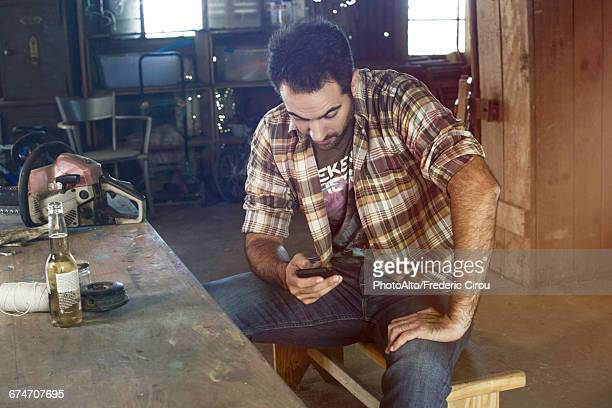 man having beer and using smartphone during break from work - feierabend stock-fotos und bilder