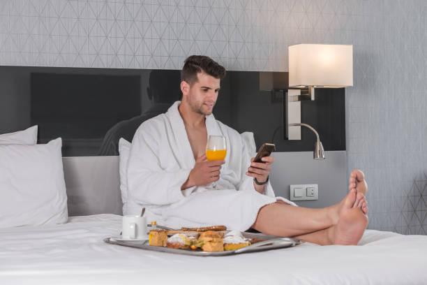 Man having breakfast and browsing smartphone in hotel bedroom