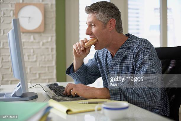 Man Having Breakfast While Using His Computer