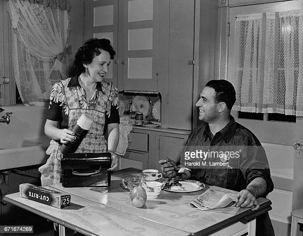 man having breakfast while woman standing beside and smiling - {{ contactusnotification.cta }} stock pictures, royalty-free photos & images