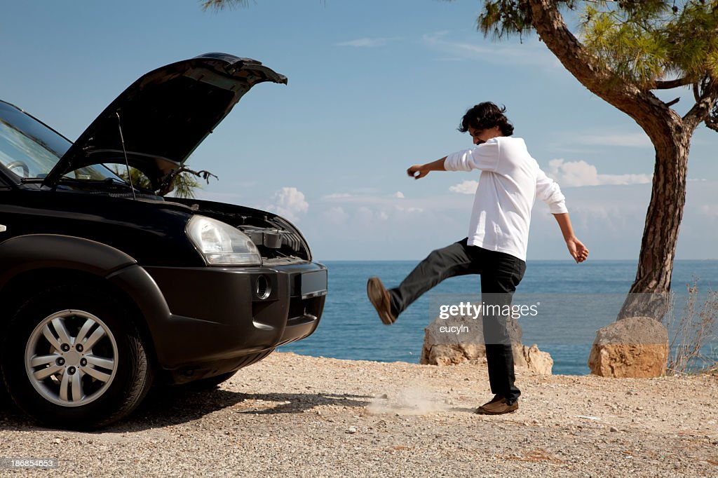 Man having car problems kicking dirt in frustration : Stock Photo