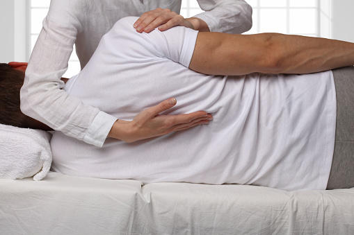 Man having chiropractic back adjustment. Osteopathy, Alternative medicine, pain relief concept. Physiotherapy, sport injury rehabilitation 671014434