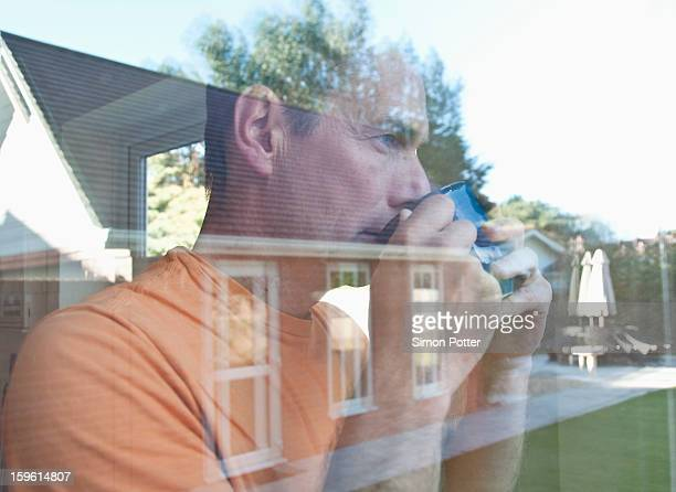 Man having coffee reflected in window