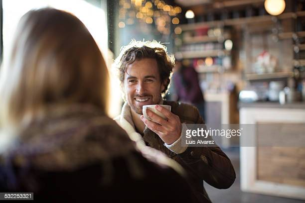 Man having coffee while looking at woman in cafe