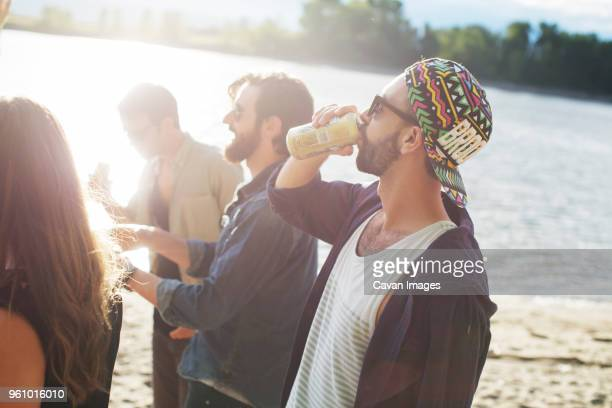 Man having drink while standing with friends against river
