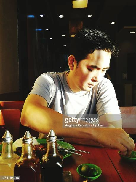 Man Having Food While Sitting At Table In Restaurant