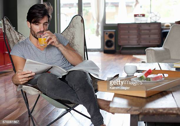 man having fresh orange juice, reading the paper