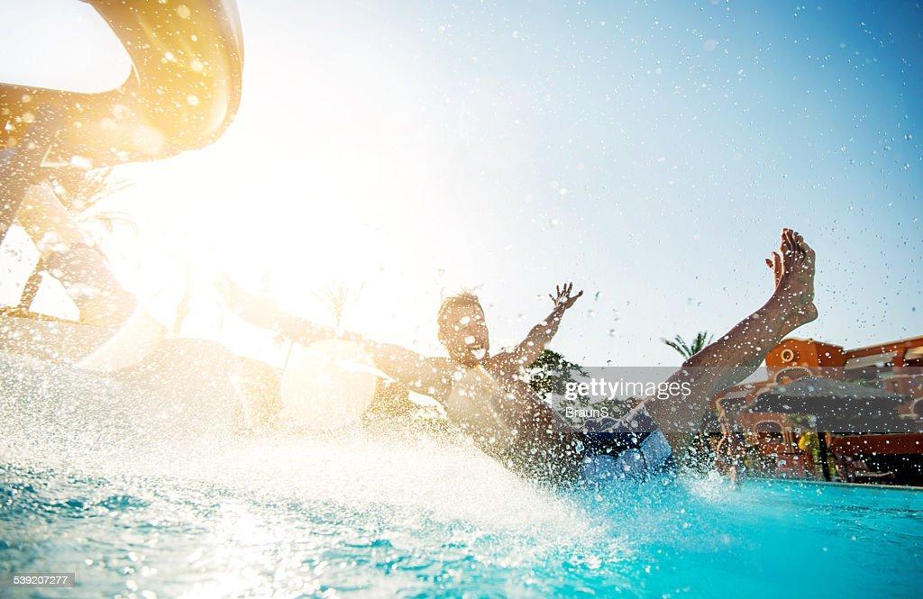 Man having fun on water slide. : Stock Photo