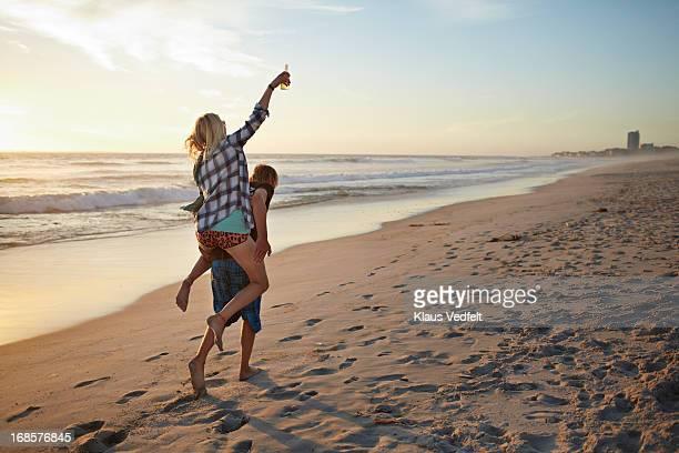Man having girlfriend on the back on the beach