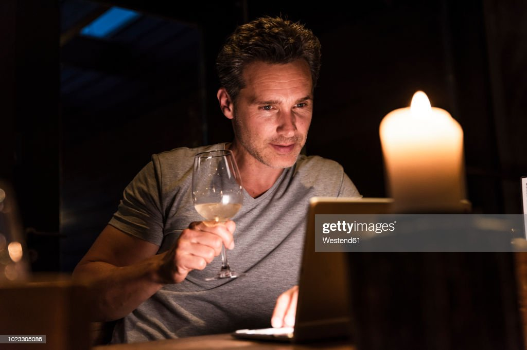 Man having glass of white wine looking at laptop : Stock Photo
