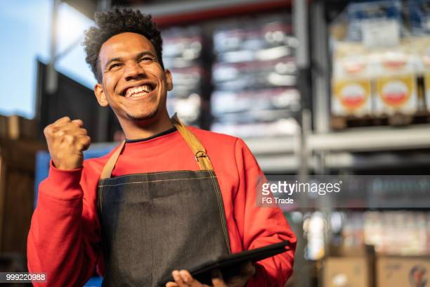 man having good news on tablet at a warehouse - making money stock pictures, royalty-free photos & images