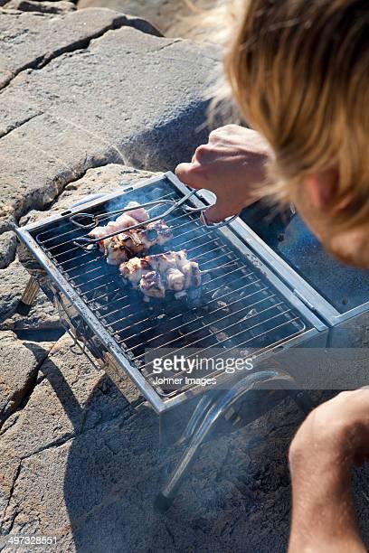 man having grill, grundsund, bohuslan, sweden - västra götalands län stockfoto's en -beelden