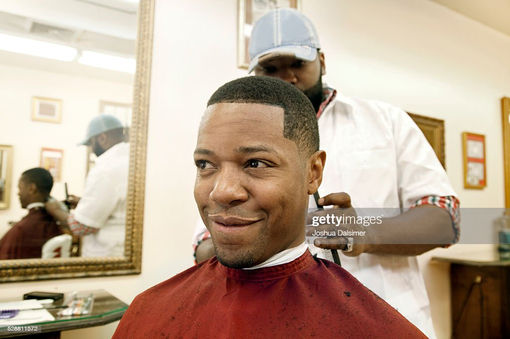 Man having hair cut in barber shop : Stock Photo