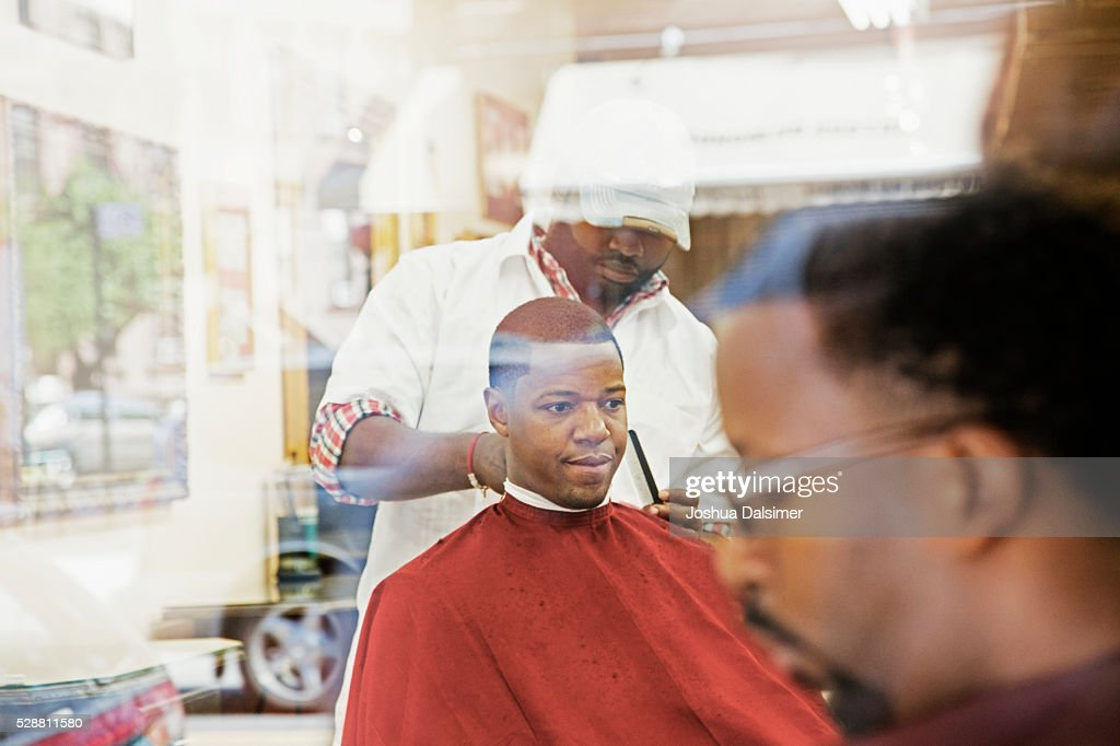 Man having hair cut in barber shop : Stock Photo