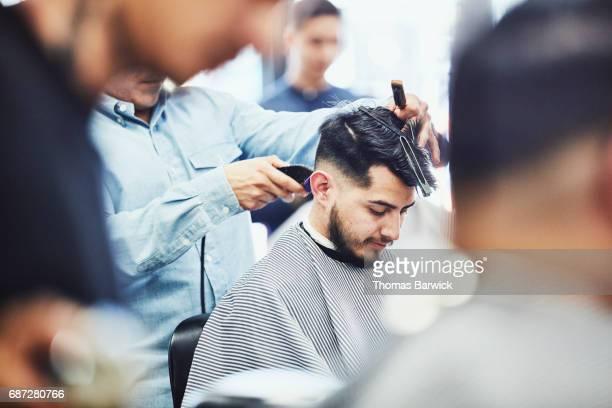 Man having hair cut in barber shop