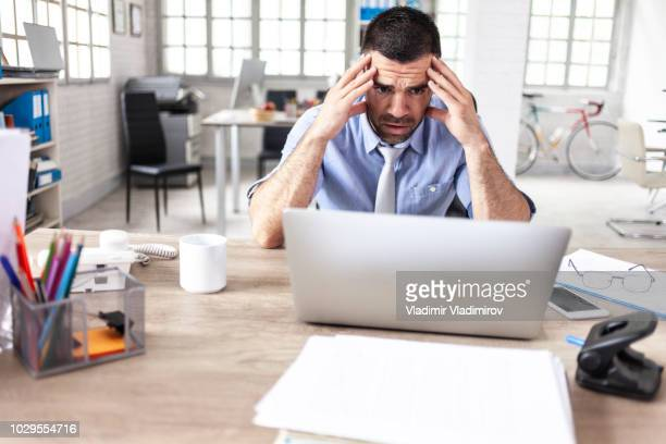 man having headache at work - stock trader upset stock pictures, royalty-free photos & images