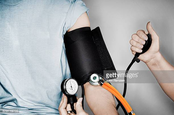 man having his blood pressure checked - blood pressure gauge stock pictures, royalty-free photos & images