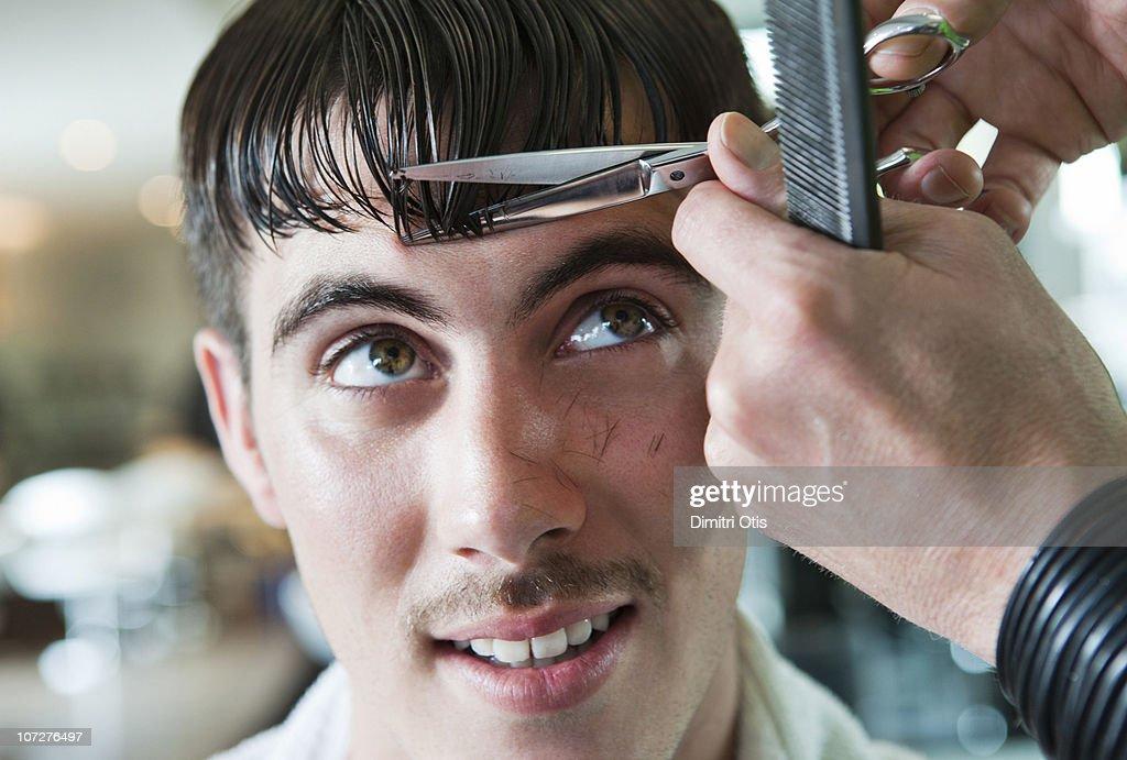 Man having his fringe cut by hairdresser : Stock Photo