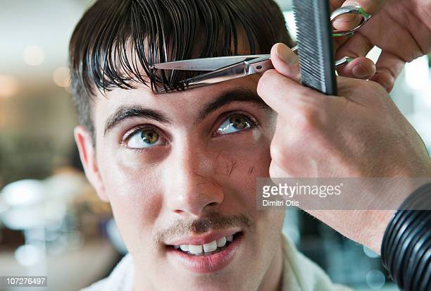 man having his fringe cut by hairdresser - fringe stock pictures, royalty-free photos & images
