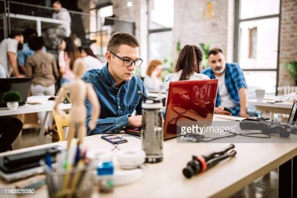 man having his job done at coworking office - reusable stock pictures, royalty-free photos & images