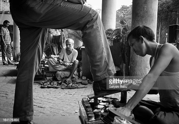 Man having his shoe polished from a footpath cobbler in Kolkata