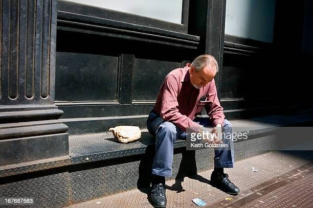 CONTENT] A man having just ate lunch is lost in thought beside a building in the Chelsea area of New York City