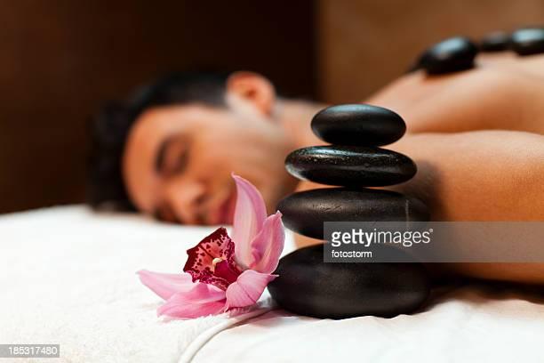man having lastone therapy - erotische massage stockfoto's en -beelden