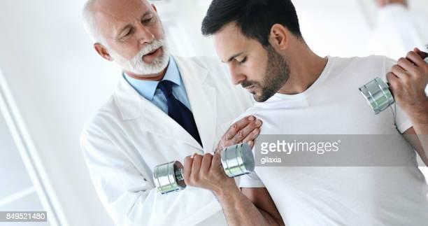 man having light rehabilitation exercise. - rheumatism stock pictures, royalty-free photos & images