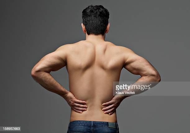 man having lower back pain (rear view) - ontbloot bovenlichaam stockfoto's en -beelden